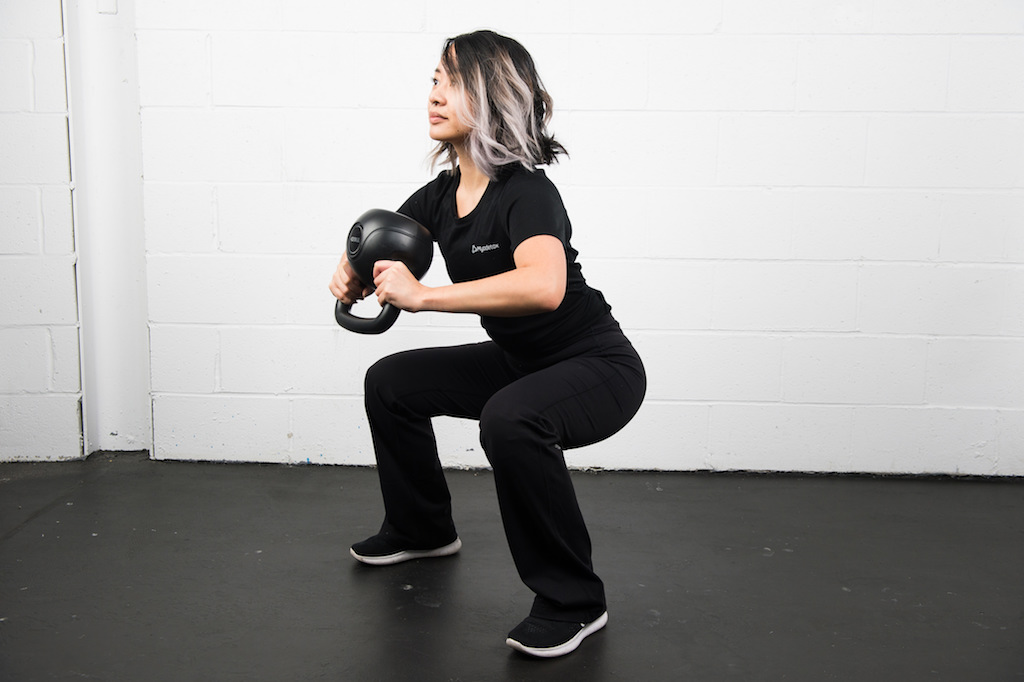 Girl squatting with kettlebell