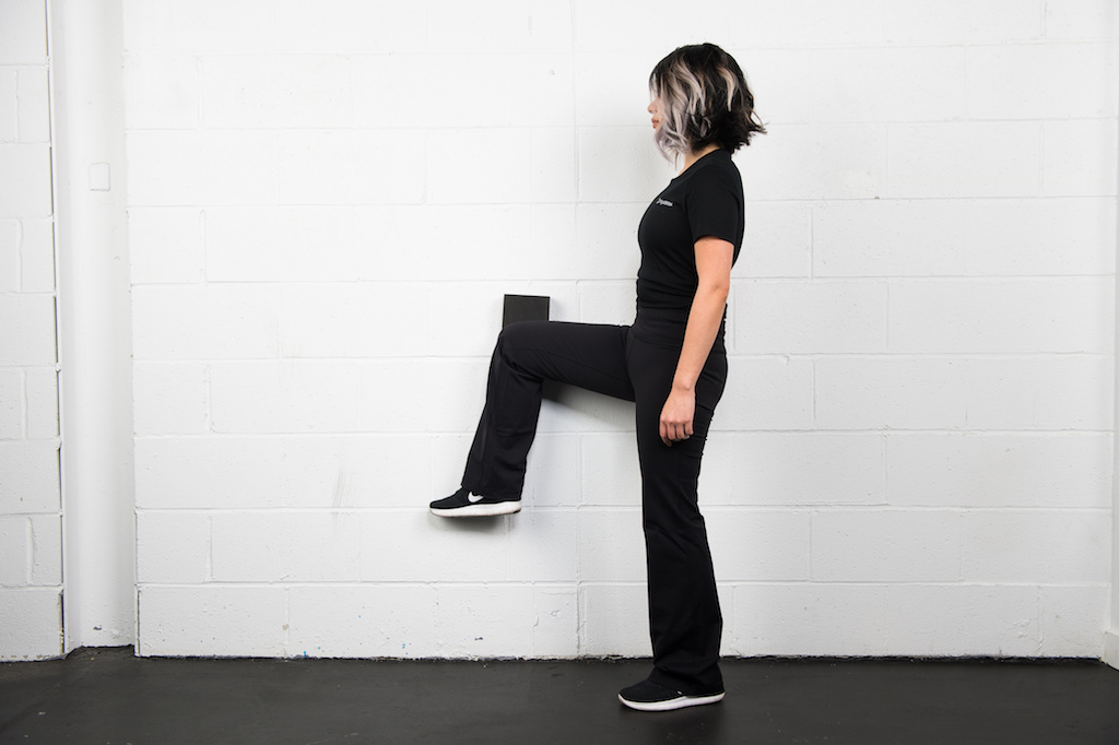 Girl with one leg pressed against wall